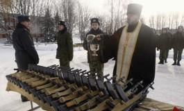 Preot sfinţind mitralierele
